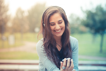 young beautiful brunette woman listening music with headphones