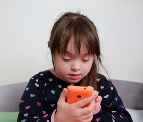 Little girl playing with phone at home