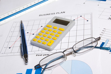 business papers with graphs, charts, glasses, pen and calculator