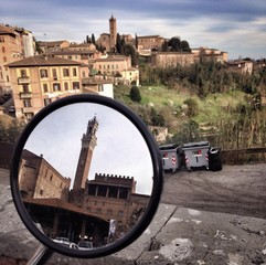 Mirror reflection of Torre del Mangia against Siena cityscape.
