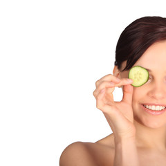 Young woman with cucumber slices on the face in a spa