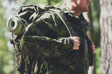 close up of young soldier with backpack in forest