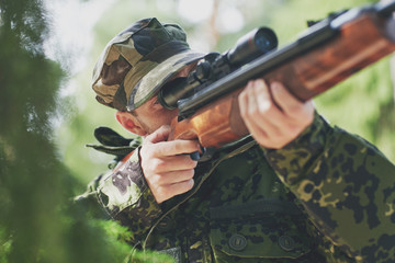 soldier or hunter shooting with gun in forest