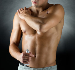 young male bodybuilder applying pain relief gel