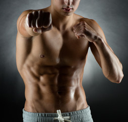 young man on fighting stand over black background