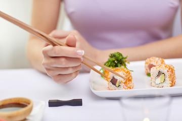 close up of woman eating sushi at restaurant