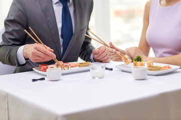 close up of couple eating sushi at restaurant