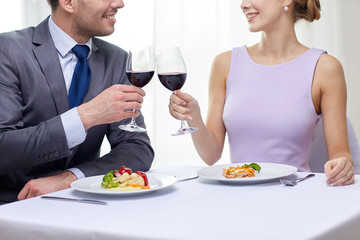 happy couple with glasses of wine at restaurant