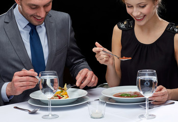 close up of couple eating at restaurant