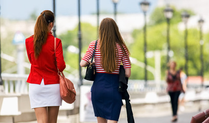 Two young women friends walking on the street
