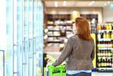 woman with shopping trolley in supermarket