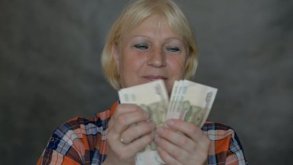 Aged woman counting money. Selective focus on face.