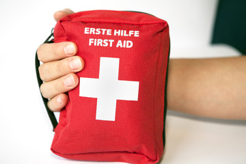 First aid kit with hand - english and german tittle