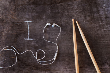 Drumsticks and earphones laid on a wooden desk background