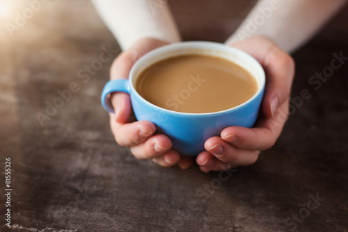 Unrecognizable woman holding a cup of coffee in her hands