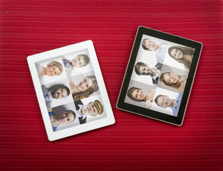 Two tablets with faces of people. Studio shot on red background.
