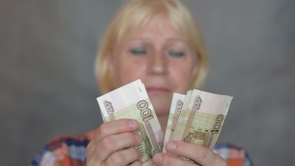 Sad woman counting money in her hand. Selective focus on money.