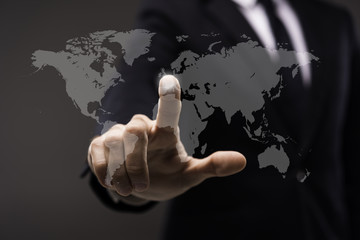 Business man touching imaginery screen with world map