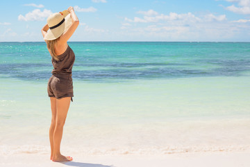 Woman with straw hat standing on the beach