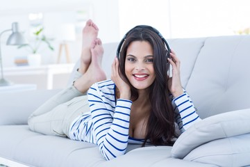 Smiling beautiful brunette listening music on couch