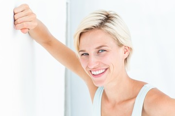 Happy woman smiling at camera with hand on wall