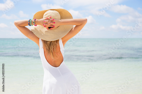 Young woman in white dress and summer hat on the beach