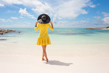 Fashionable woman in yellow dress on the beach