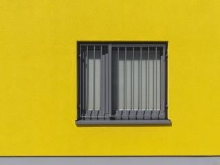 Vergittertes Fenster in einer gelben Fassade in Großauheim