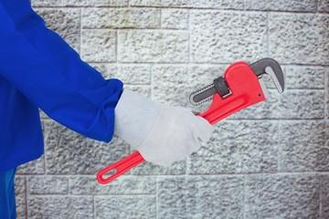 Composite image of mechanic holding monkey wrench