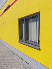 Knallgelbe Hauswand mit vergittertem Fenster in Großauheim