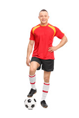 Young male soccer player standing over a ball