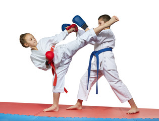 The girl with a red belt kicks the boy with a blue belt