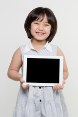 Little asian girl smiling and holding tablet computer