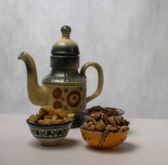 чайник в восточном стиле и пиалы с изюмом и орехами