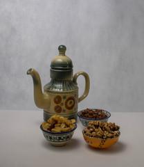 Чайник в восточном стиле и пиалы с изюмом на белом фоне