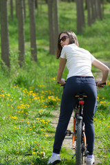 Young woman cyclist in the forest park recreation