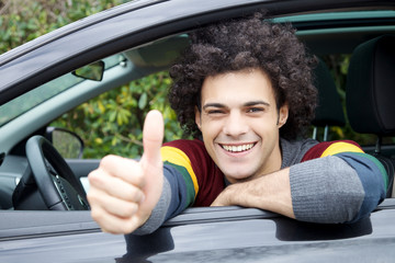 Happy handsome man thumb up sitting in car
