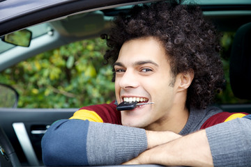 Happy man with key of new car in mouth smiling