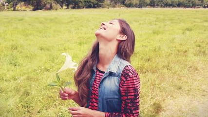 Pretty brunette smelling a flower