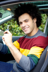Young cool man showing key sitting in car
