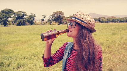 Happy hipster drinking beer in the park