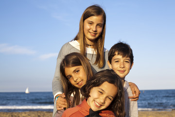 Niños en la playa con velero al fondo