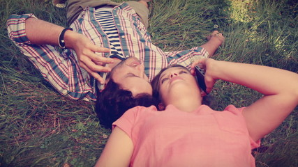 Cute couple lying on the grass and having a phone call