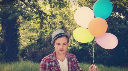Handsome hipster holding balloons