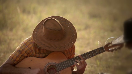 Romantic cowboy in hat is playing acoustic guitar and sing song