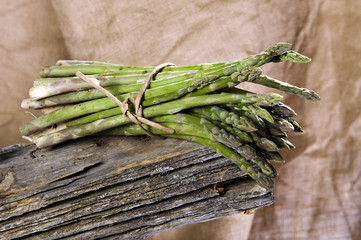 Asparagus on a wooden background and is raffia