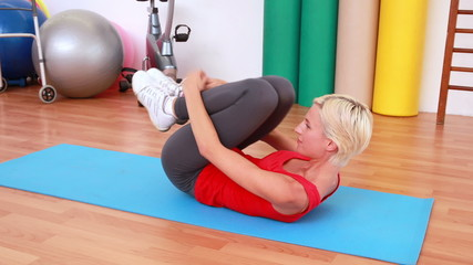 Blonde woman working on exercise mat