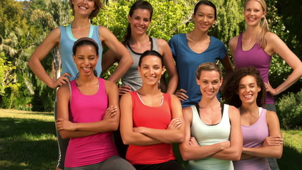 Fitness group smiling at camera in park