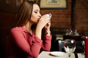 Woman drinking coffee in a restaurant