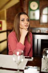 Sad beautiful woman in a restaurant